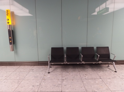 Bench at Terminal 2, Heathrow airport by a Help sign