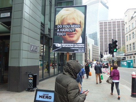 Advertising placard seen on Fenchurch Street using Boris Johnson's unruly mop to advertise a local barber's shop